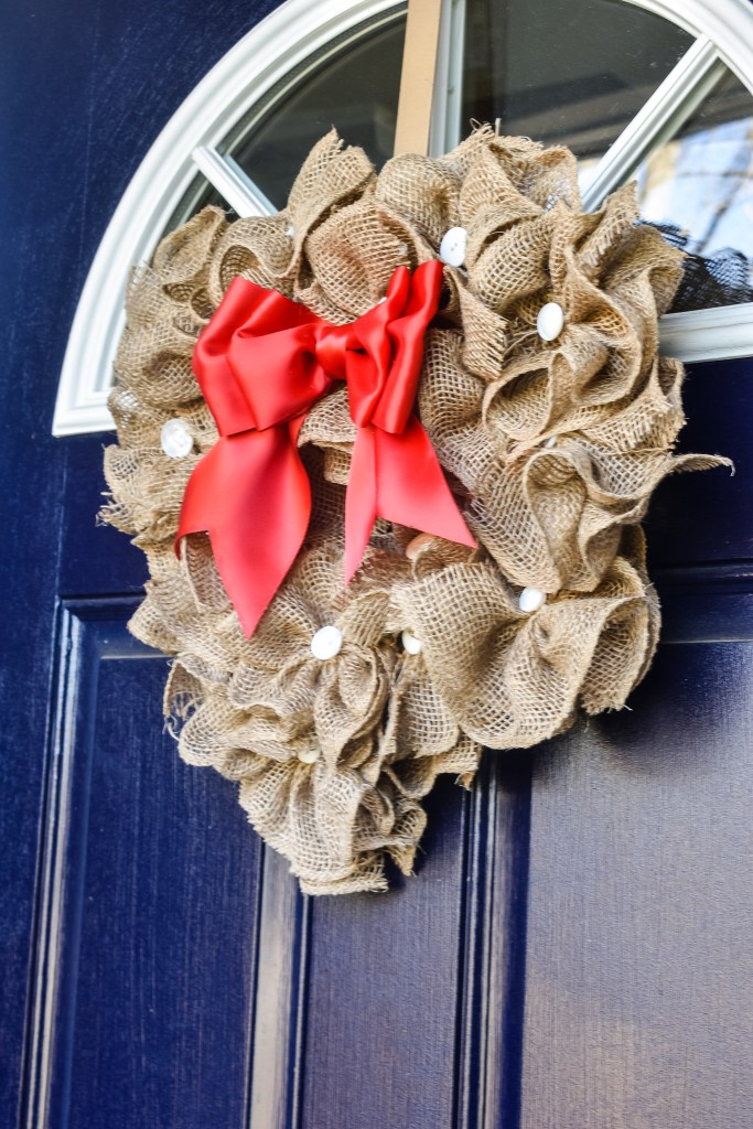 Heart shaped Valentine's Day DIY burlap wreath with red bow and white buttons on a blue door