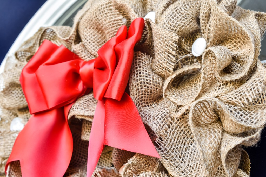 DIY burlap wreath with red bow and white buttons