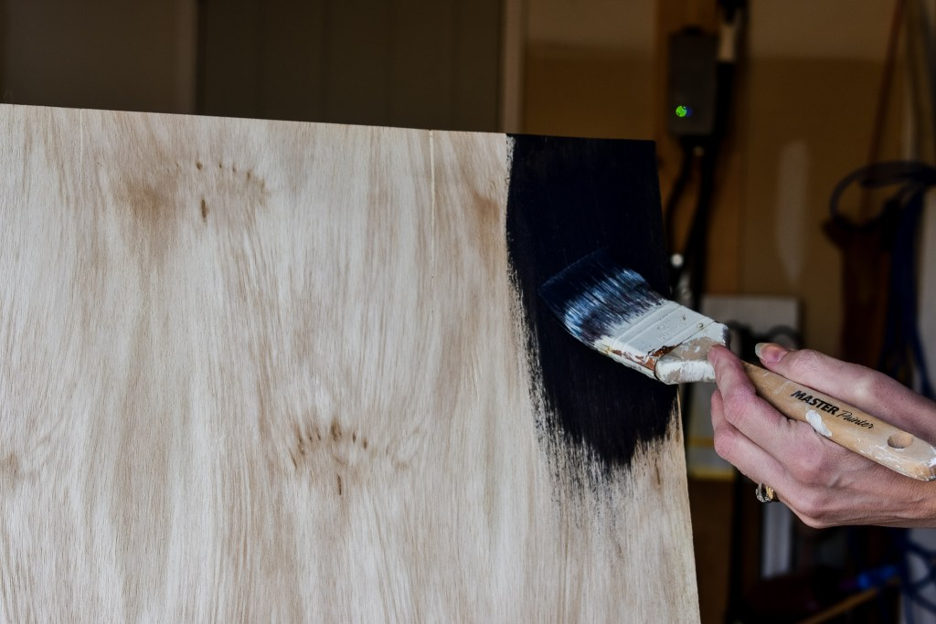 Painting a piece of plywood with chalkboard paint to create a DIY chalkboard