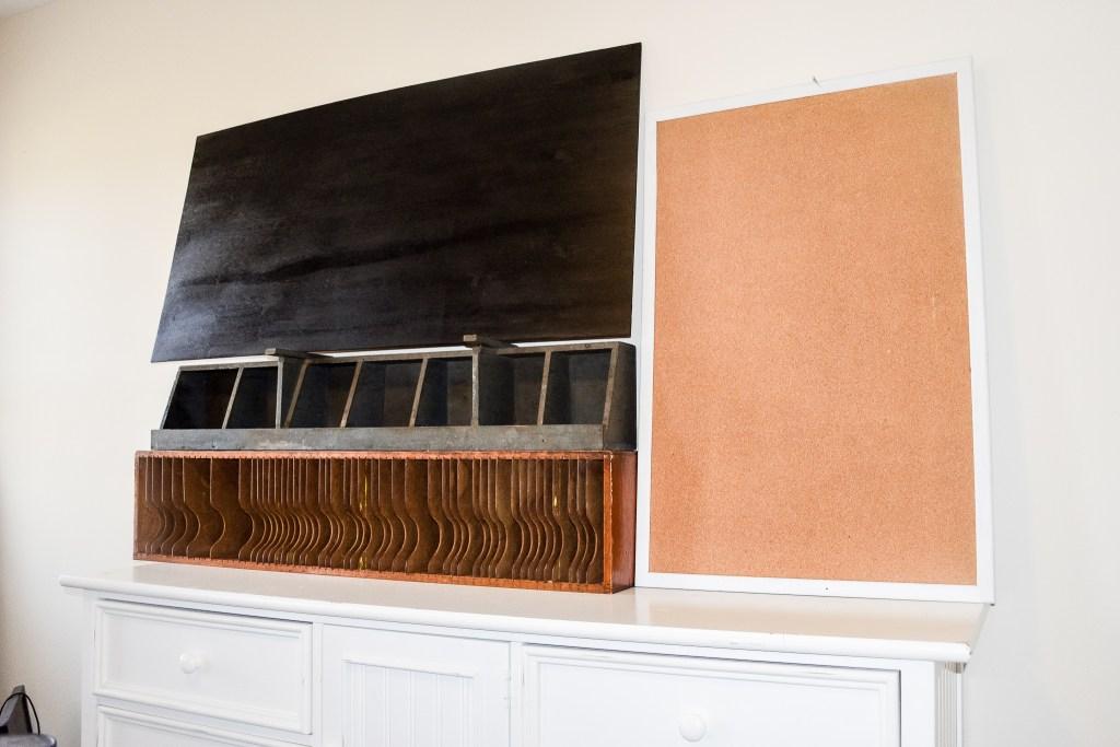 DIY chalkboard, bulletin board, vintage mail sorter and cubbies atop a dresser