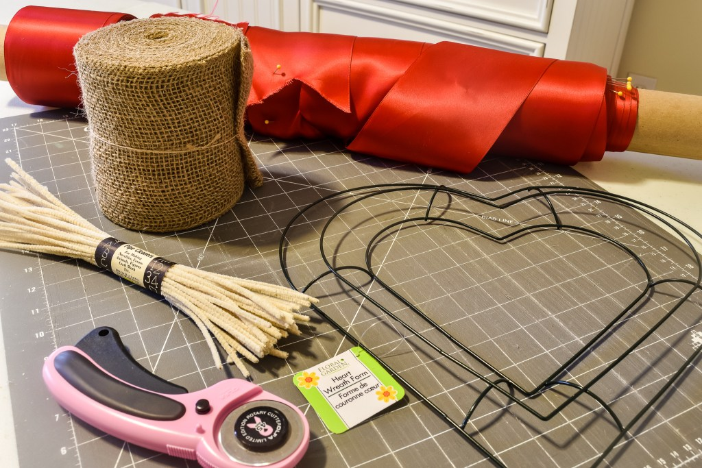 Roll of burlap, red ribbon, heart wreath form, & pipe cleaners to make a DIY Burlap Wreath