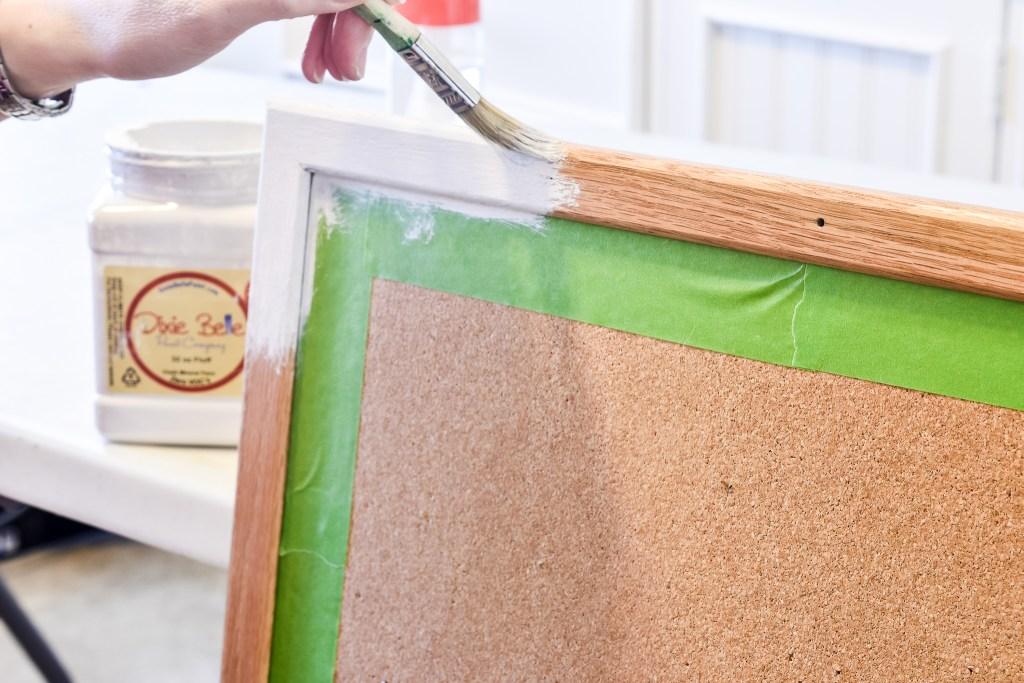 Painting the trim white of an inspiration bulletin board for a craft room makeover