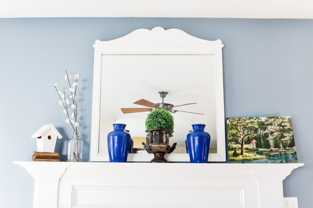 How to decorate a large mantel for  spring using tall decorative accents, artwork and faux florals