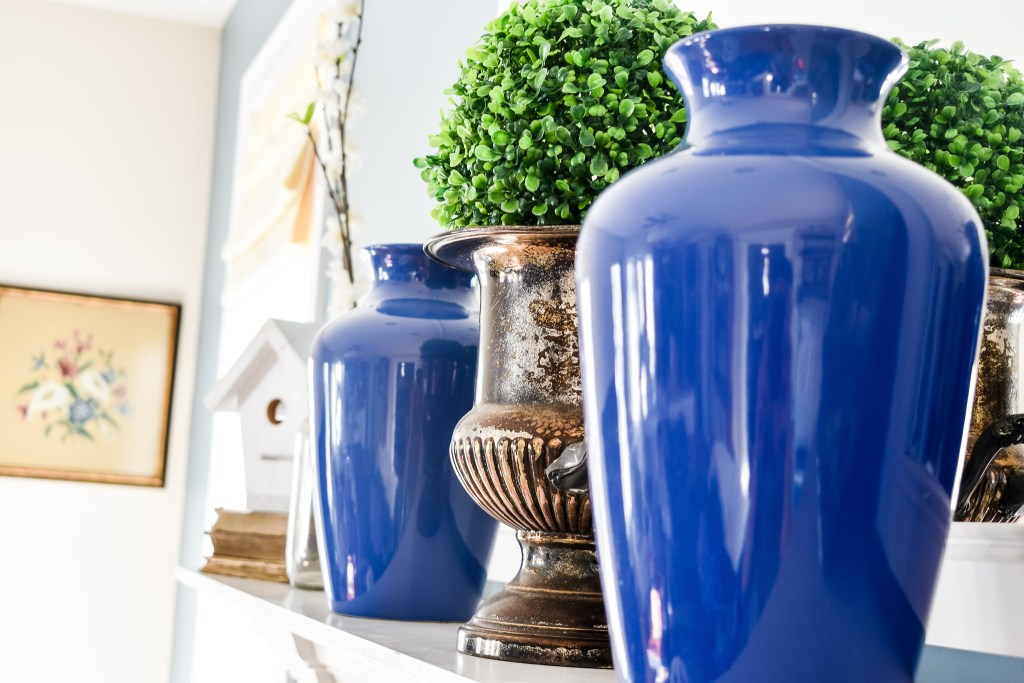 side view of two blue vases and a tarnished urn with a faux boxwood ball on a Spring mantel