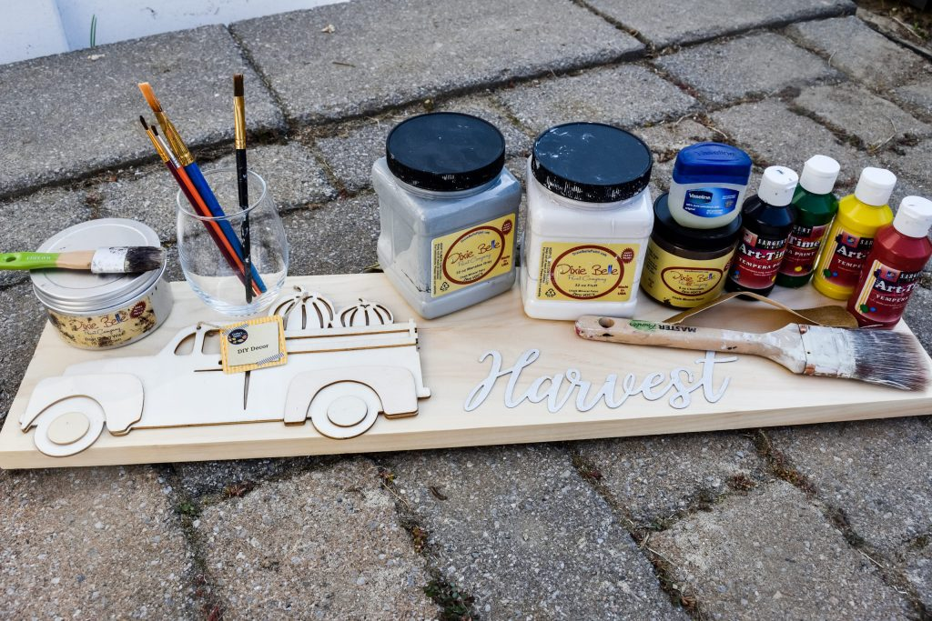 pumpkin truck wood cutout, metal harvest word, paint, wax, wooden board, paintbrushes and sandpaper