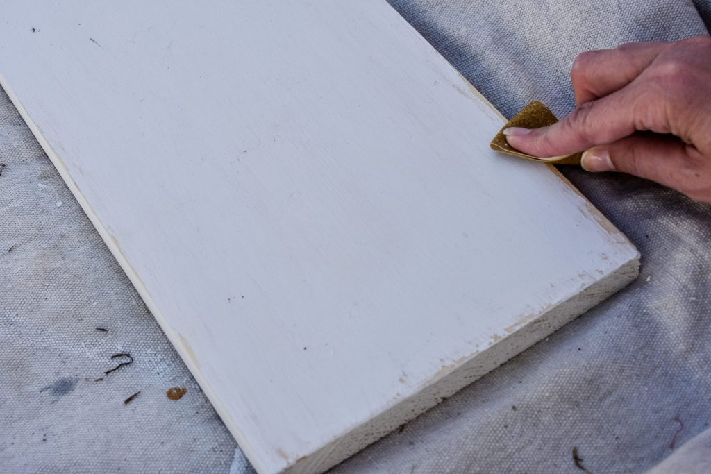 sanding a painted white board by hand