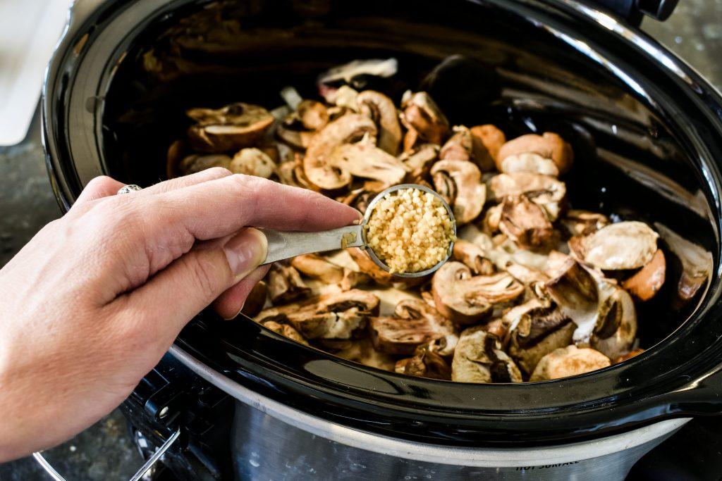 adding minced garlic to a crock pot