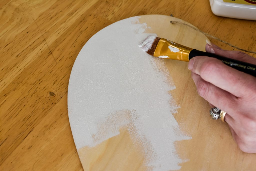 painting a wooden heart cut out with white paint