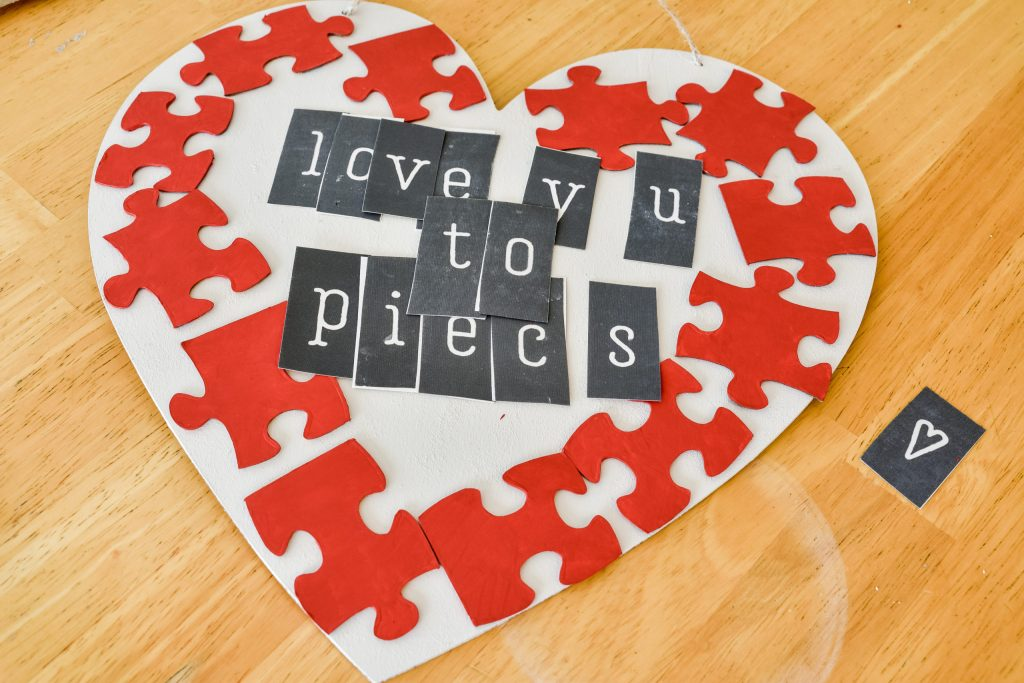 """arranging stencils with the phrase """"love you to pieces"""" in the middle of a white painted wooden heart"""