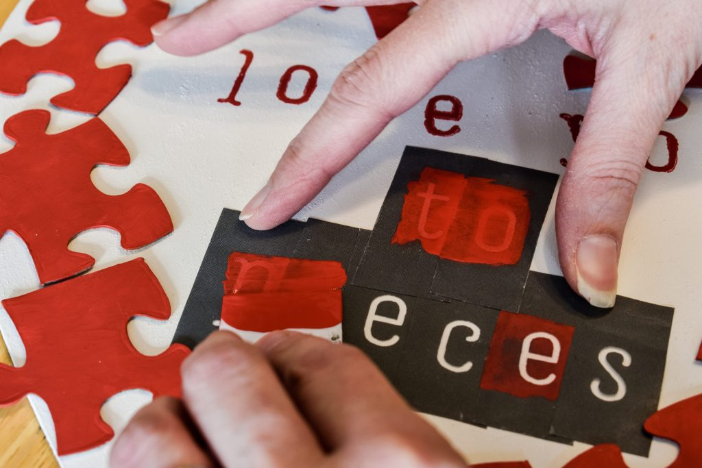 applying red paint to letter stencils