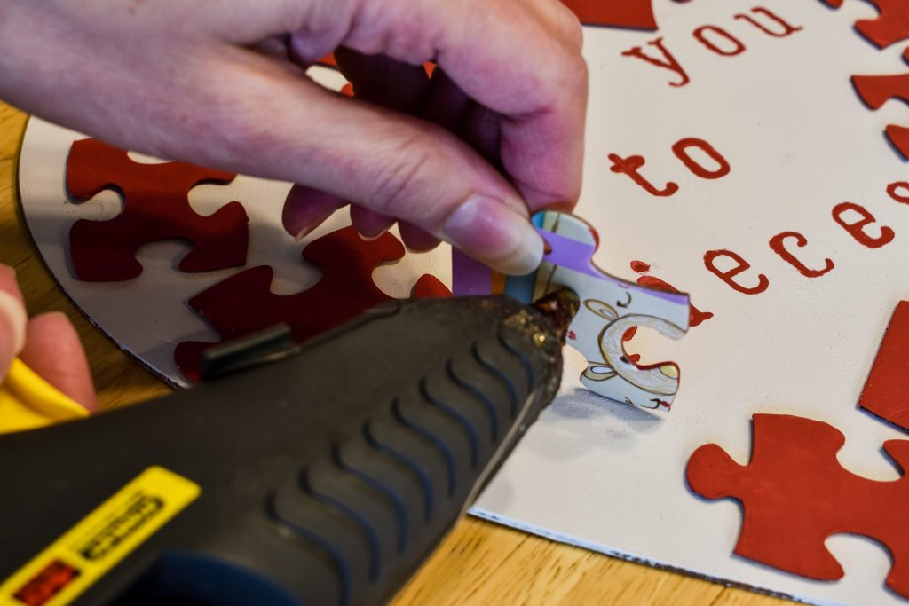 applying hot glue to a puzzle piece
