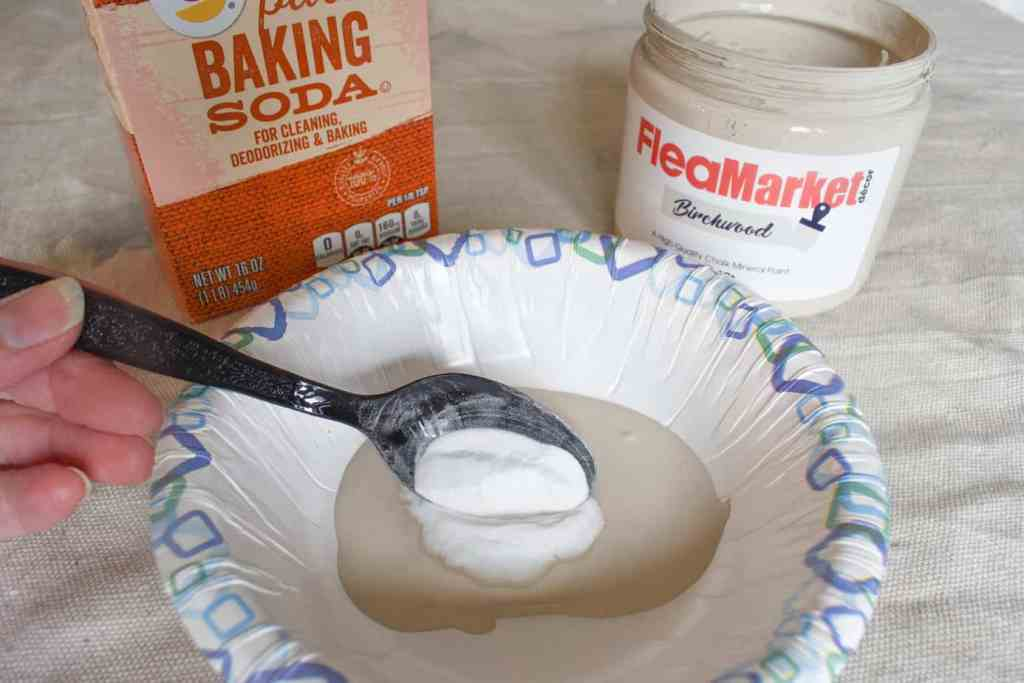 spooning baking soda into a bowl with chalk paint