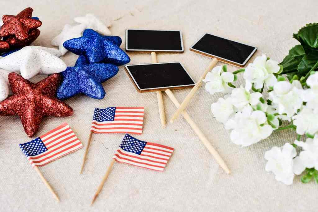 red white and blue patriotic home decor accents from Dollar Tree including red white and blue glittered star table scatters and mini American flags