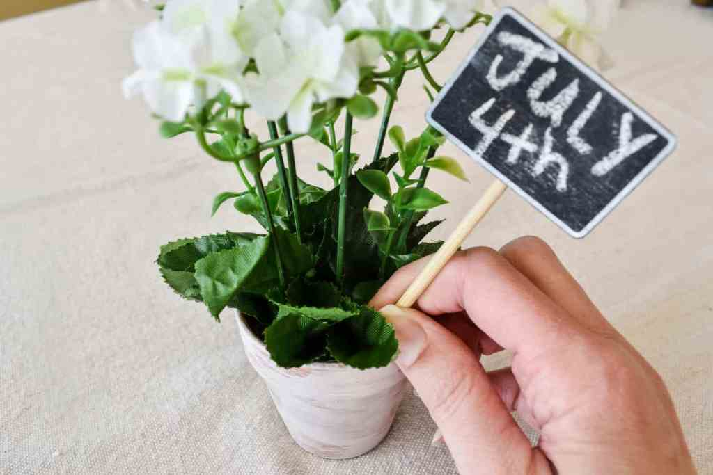 """putting a mini chalkboard on a stick labeled """"July 4th"""" into a small pot of faux white flowers"""