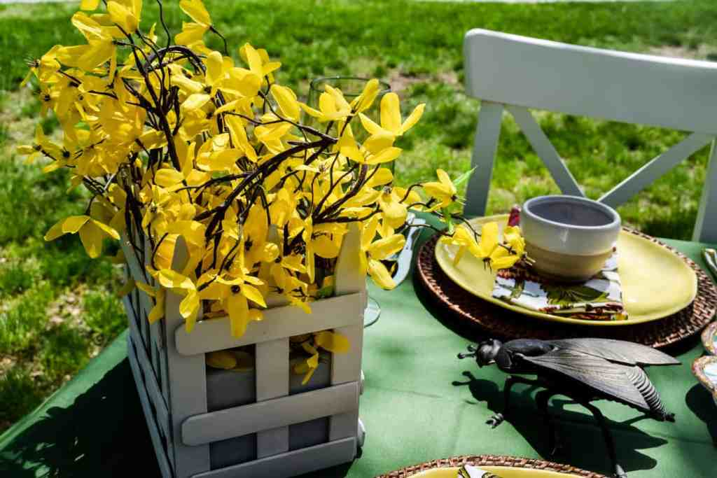 white picket fence planter filled with faux yellow forsythia