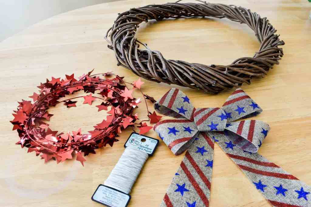 grapevine wreath form, burlap bow with red stripes and blue stars, red star garland and silver florist wire