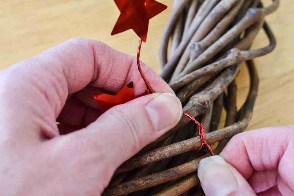 tying a red star garland to a grapevine wreath form