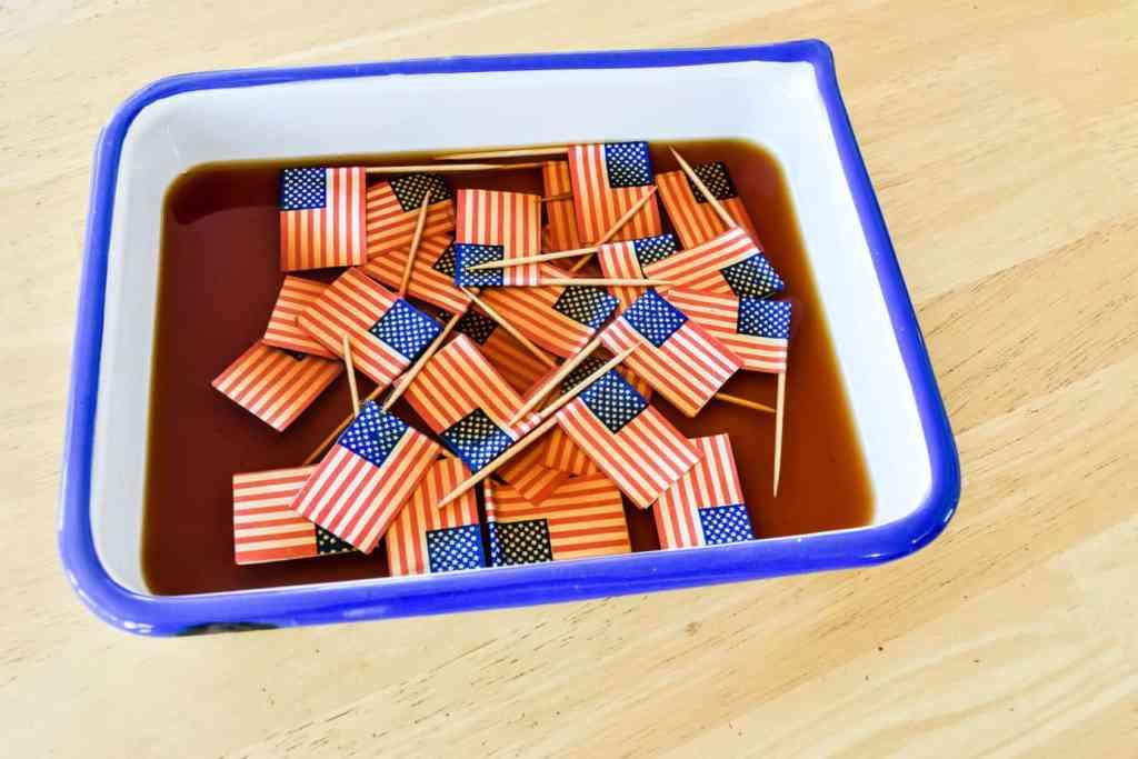 mini paper American flags being tea dyed in an enamel pan