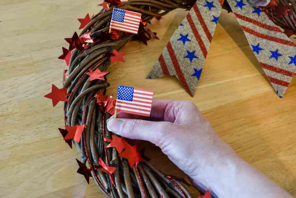 arranging mini American flags on a patriotic door wreath