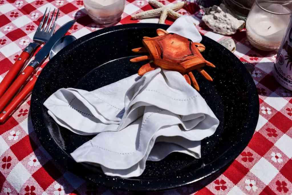 black enamelware plate with an orange crab napkin ring holding a white linen napkin