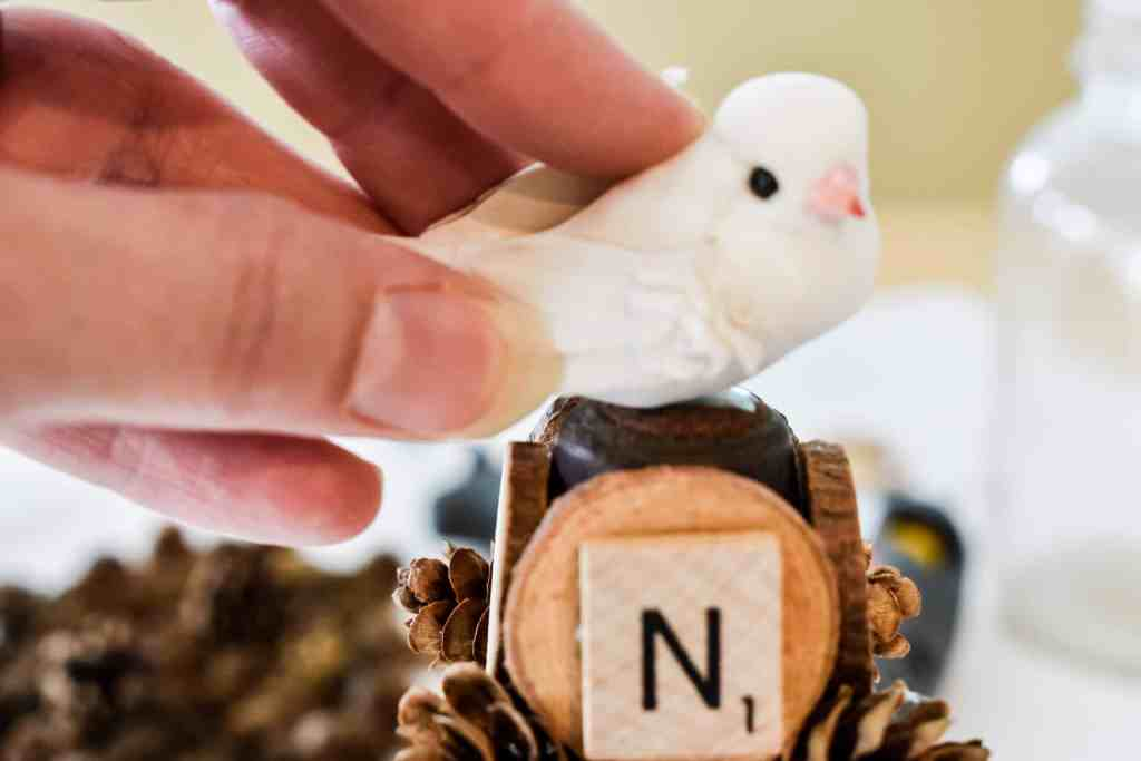 placing a white faux bird on the top of a rustic wooden Christmas tree decorated with small wood slices, pinecones and Scrabble tiles
