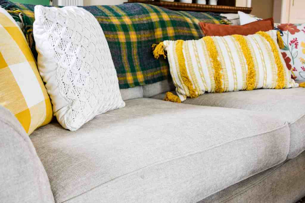 five pillows on a couch in a yellow, orange and green color palette including floral, striped and buffalo check patterns