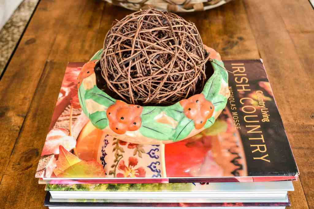 orange and green vintage bowl filled with a grapevine orb set atop a stack of books on a coffee table