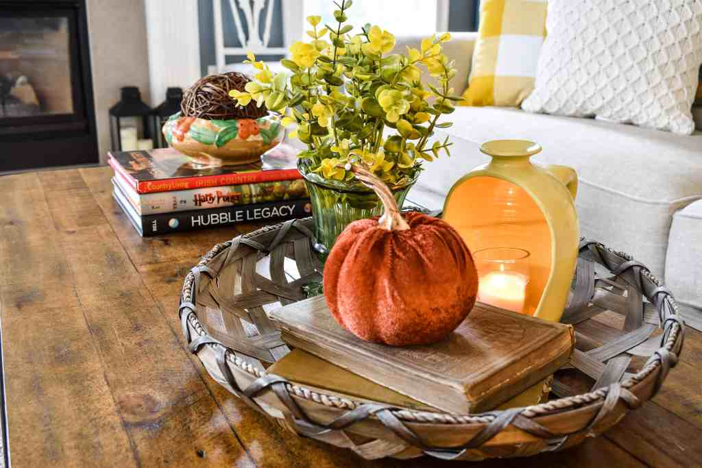 basket tray on a coffee table filled with an arrangement of faux florals, a yellow half jug lit lantern and a rust colored velvet pumpkin on top of old books