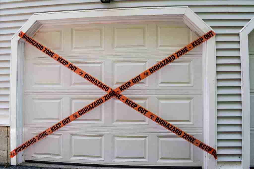 biohazard tape hung in a criss cross pattern on a garage door as part of zombie themed garage door halloween decorations