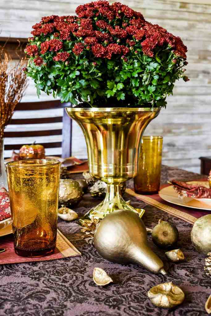 maroon colored mums in a gold urn on a fall tablescape