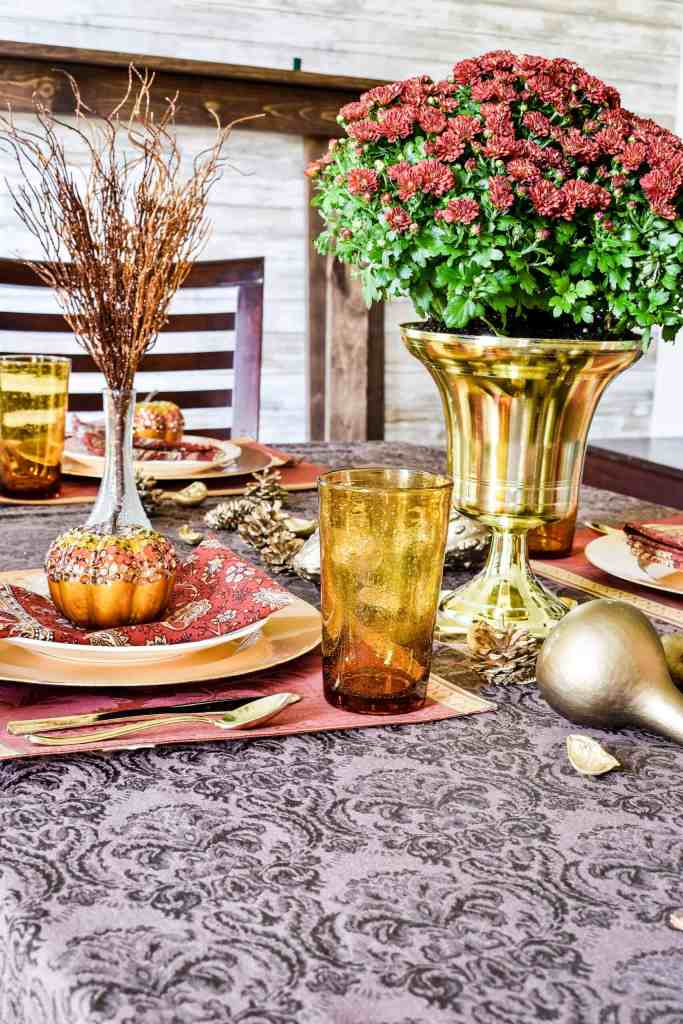 glam pumpkin covered with sequins on top of a place setting on a fall tablescape with a mum centerpiece.
