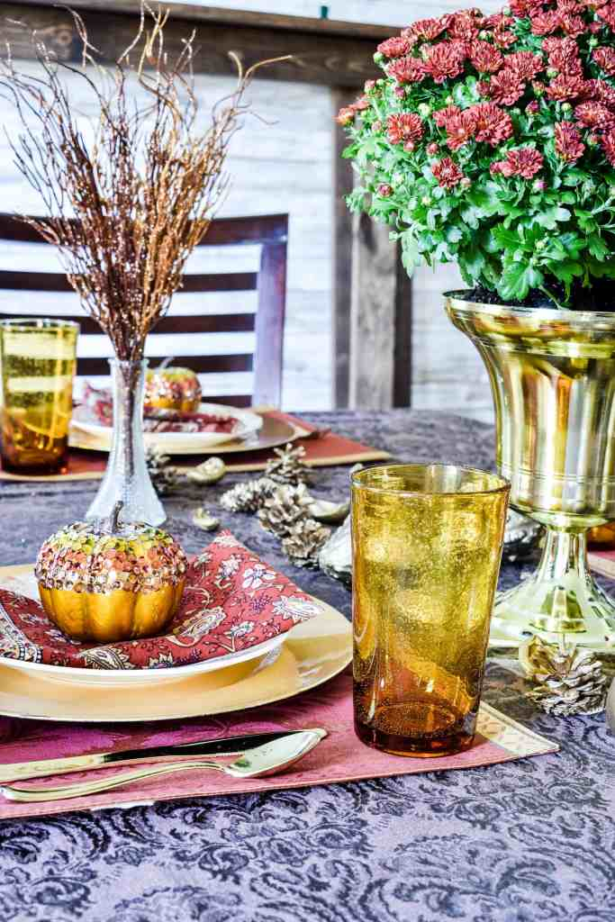 glam pumpkin covered with sequins on top of place setting on a  fall tablescape with a mum centerpiece.