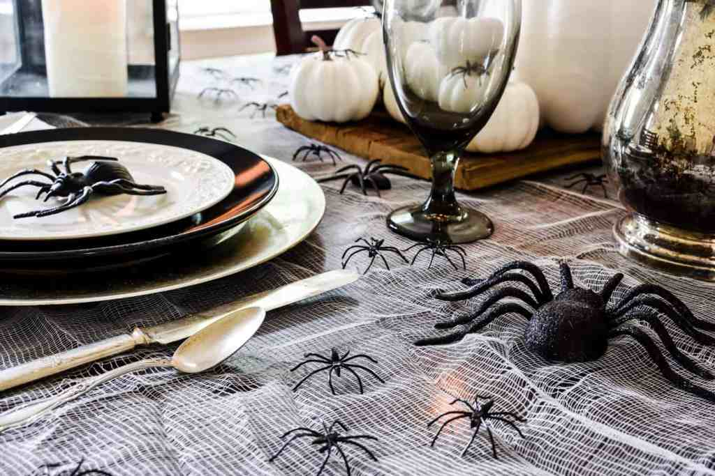 cheesecloth tablecloth covered with black plastic spiders on a Halloween tablescape