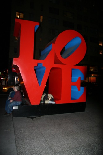 Homeless man sleeping on LOVE sign, New York