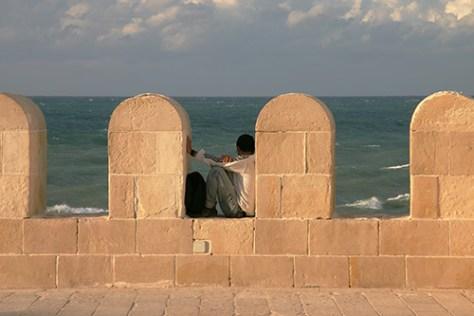 Man sits in Qaitbay Citadel wall, Alexandria, Egypt