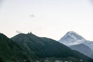 Widok na kościółek i Kazbek z miejscowości Stepancminda Gruzja