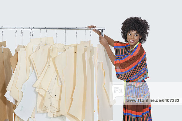 african american female designer with sewing patterns on clothes rack over gray background