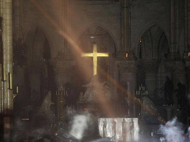 Photo of the Gold Cross shining amidst the debris of Notre Dame Cathedral.