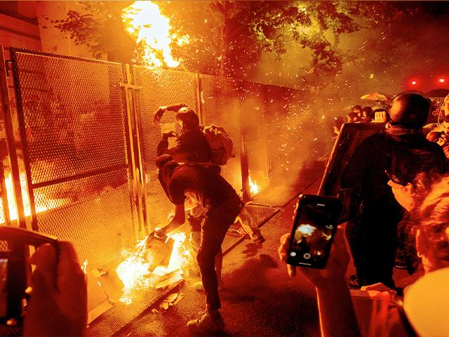 Protesters throw flaming debris over a fence at the Mark O. Hatfield US Courthouse on July 22, 2020, in Portland, Ore. following a larger Black Lives Matter Rally (AP Photo/Noah Berger)