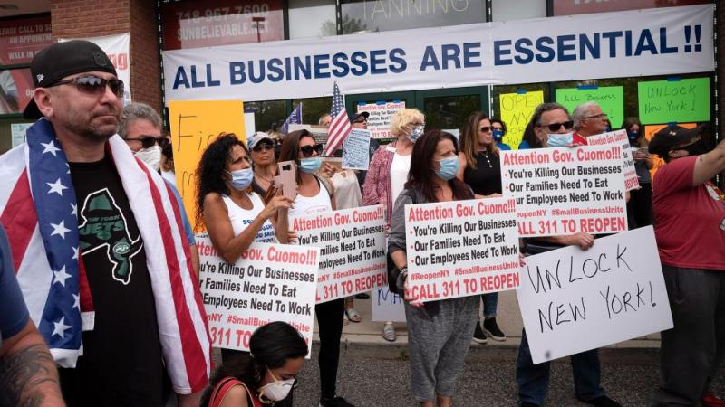 A crowd of supporters shows up for Bobby Catone, the owner of a Staten Island tanning salon, May 28, 2020, in NY. He opened the salon in defiance of a law requiring non-essential businesses to remain closed (AP Photo/Mark Lennihan)