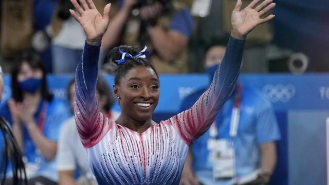 Simone Biles, of the United States, waves after performing on the balance beam during the artistic gymnastics women's apparatus final at the 2020 Summer Olympics, Tuesday, Aug. 3, 2021, in Tokyo, Japan. (AP Photo/Ashley Landis)