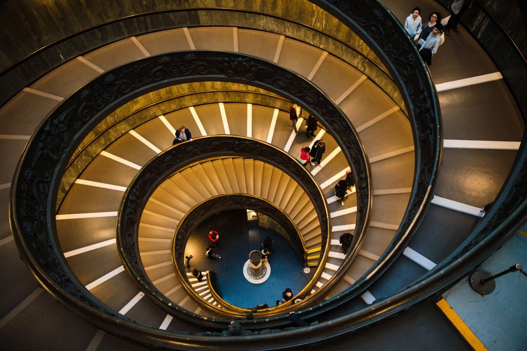 People moving down a large spiral staircase.
