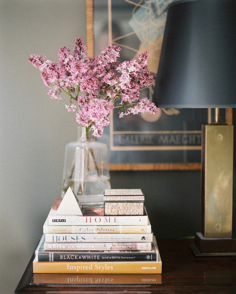 Tablescape - A brass lamp and a stack of books on a wood surface