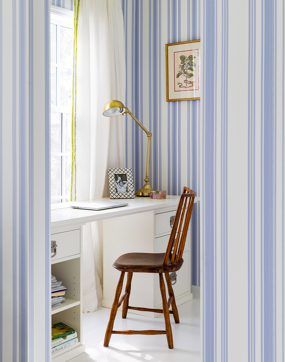 Farrow & Ball cornflower-blue wallpaper brightens up the master bedroom. An adjacent dressing room doubles as a workstation.