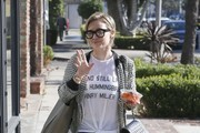 'Younger' actress Hilary Duff wears a pair of thick rimmed glasses as she steps out (with a snack of carrots) in Melrose Place on December 22, 2014 in Los Angeles, California. Hilary's shirt had a quote from Henry Miller on it, 'stand still like the hummingbird.' (The full quote reads 'either you take in believing in miracles or you stand still like the hummingbird.') Is Hilary making a statement with her shirt, or is she just a fan of Henry Miller?