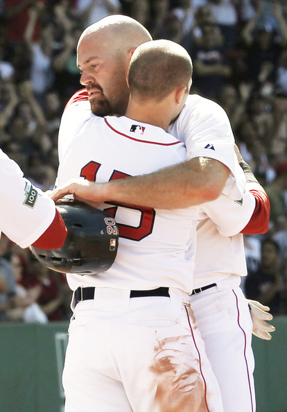 Dustin Pedroia Kevin Youkilis #20 of the Boston Red Sox is hugged by teammate Dustin Pedroia #15 after being taken out of the game during the seventh inning of the interleague game against the Atlanta Braves at Fenway Park on June 24, 2012 in Boston, Massachusetts.