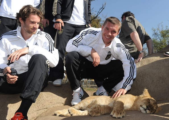 Arne Friedrich Lukas Podolski (L) and Arne Friedrich of the German National Team stroke a lion cup during a visit at the Lion Park on June 25, 2010 in Lanseria, South Africa.