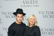 """Nick Jonas (L) and Victoria's Secret CEO Sharen Turney attend Russell James' """"Angel"""" book launch hosted by Victoria's Secret on September 10, 2014 in New York City."""