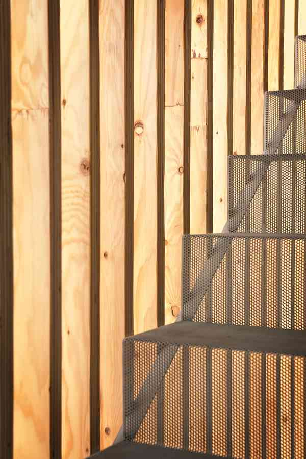 Detail at stair: wood slats and perforated metal stair