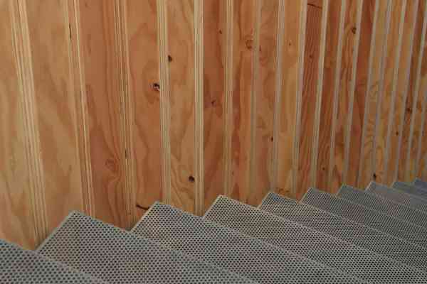 Detail at perforated metal stair and wood slat wall